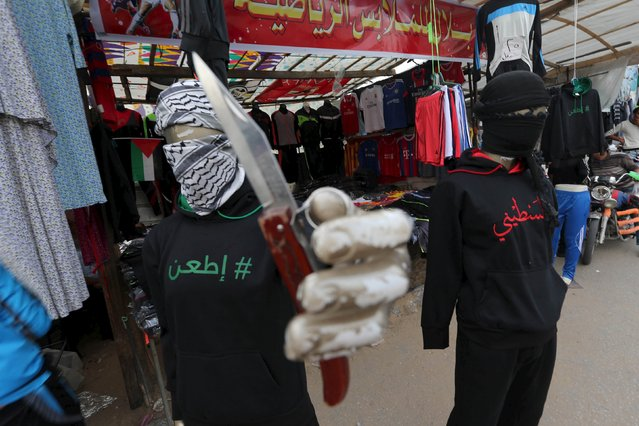 "A mannequin holding a knife displaying a jacket that reads ""stab"" (L) is seen outside a clothes shop in Khan Younis, in the southern Gaza Strip November 3, 2015. The shop owner said the display was made in support of Palestinians committing stabbing attacks against Israelis. (Photo by Ibraheem Abu Mustafa/Reuters)"