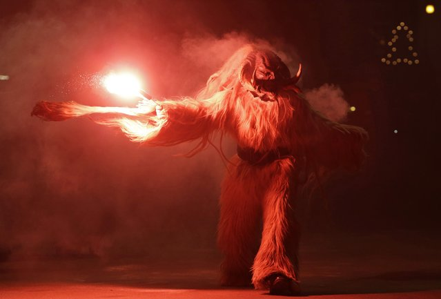 A man dressed as a devil performs during a Krampus show in the southern Bohemian town of Kaplice December 13, 2014. Each year people in traditional costumes and masks parade through the streets to perform an old ritual to disperse the ghosts of winter. (Photo by David W. Cerny/Reuters)
