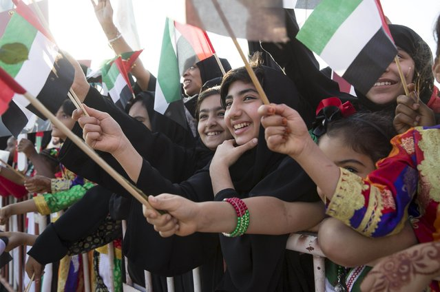 Crowd wave United Arab Emirates flags as they welcome the first batch of the UAE armed forces upon their return from Yemen in Abu Dhabi, November 7, 2015. (Photo by Reuters/United Arab Emirates News Agency WAM)