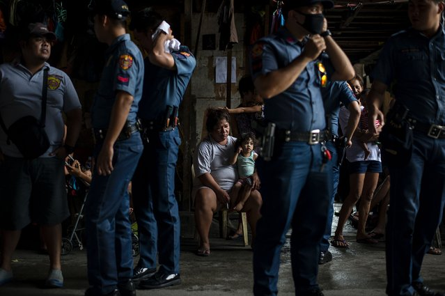 """Police officers stand as residents look at them during an """"Oplan Tokhang"""" or house-to-house campaign on illegal drugs at an informal settlers community in Manila on October 6, 2016. (Photo by Noel Celis/AFP Photo)"""