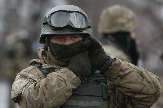 An Ukrainian serviceman checks his helmet at a checkpoint near the eastern Ukrainian town of Debaltseve in Donetsk region, December 24, 2014. (Photo by Valentyn Ogirenko/Reuters)