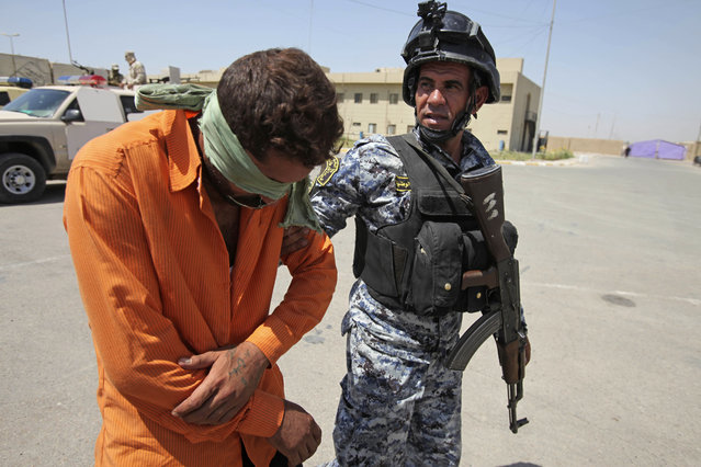 In this September 2, 2009 file photo, an Iraqi national police officer escorts a man detained in a raid that netted a large cache of weapons north of Baghdad, Iraq. A leaked U.S. diplomatic memo says Prime Minister Nouri al-Maliki accused Iran and Syria of arming insurgents in September 2009. The memo, which was recently posted on the WikiLeaks website, quotes al-Maliki as telling then-U.S. (Photo by Karim Kadim/AP Photo)