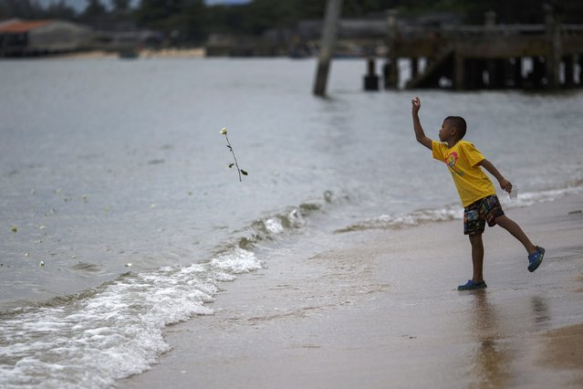 A boy throws a rose into the sea near a monument for victims of the 2004 tsunami in Ban Nam Khem, a southern fishing village destroyed by the tsunami, December 26, 2014. Survivors of Asia's 2004 tsunami and relatives of its 226,000 victims cried and prayed as they gathered along Indian Ocean shorelines on Friday for memorials to mark the 10th anniversary of a disaster that still leaves an indelible mark on the region. (Photo by Athit Perawongmetha/Reuters)