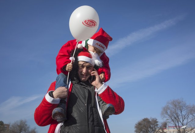 A man talks on a phone as he carries his son dressed as Father Frost, the equivalent of Santa Claus, during a parade in Almaty December 28, 2014. (Photo by Shamil Zhumatov/Reuters)