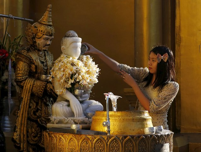A woman performs a religious ritual at Shwedagon Pagoda in Yangon, Myanmar, November 13, 2015. (Photo by Olivia Harris/Reuters)