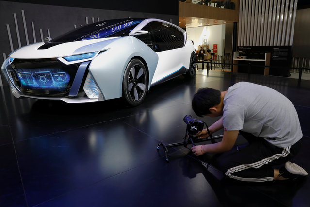 A visitor takes pictures of the Changjiang EV model during a media preview at the Auto China 2018 motor show in Beijing, China on April 25, 2018. (Photo by Damir Sagolj/Reuters)