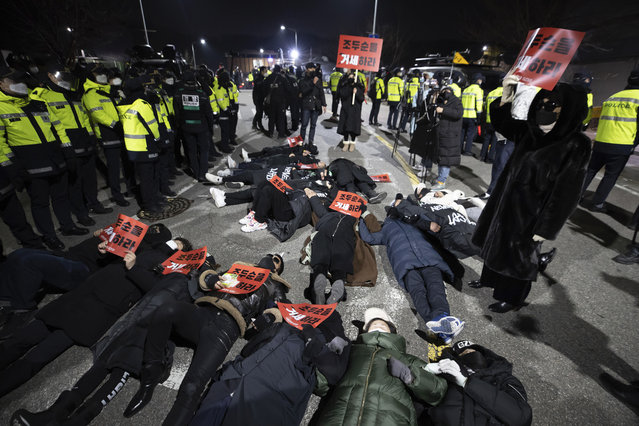 """Protesters lie down on the road to oppose the release of Cho Doo-soon in front of a prison in Seoul, South Korea, Saturday, December 12, 2020. Angry protesters threw eggs and shouted insults as Cho, one of South Korea's most notorious child predators, was released from a prison in southern Seoul on Saturday at the end of a 12-year term. The signs read: """"Let's castrate Cho Doo-soon"""". (Photo by Yun Dong-jin/Yonhap via AP Photo)"""