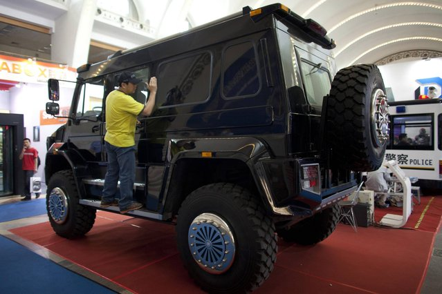 A man checks the interior of a Mercedes-Benz Unimog U5000 four-wheel-drive truck exhibited at a police equipment expo in Beijing, China, Wednesday, May 15, 2013. Chinese government spending on police, courts and other law enforcement to maintain social stability is projected to exceed outlays for national defense for the third year in a row this year. (Photo by Alexander F. Yuan/AP Photo)