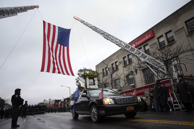 The lead funeral procession vehicle for NYPD officer Wenjian Liu makes its way under a US flag en route to the cemetery in the Brooklyn borough of New York January 4, 2015. (Photo by Shannon Stapleton/Reuters)