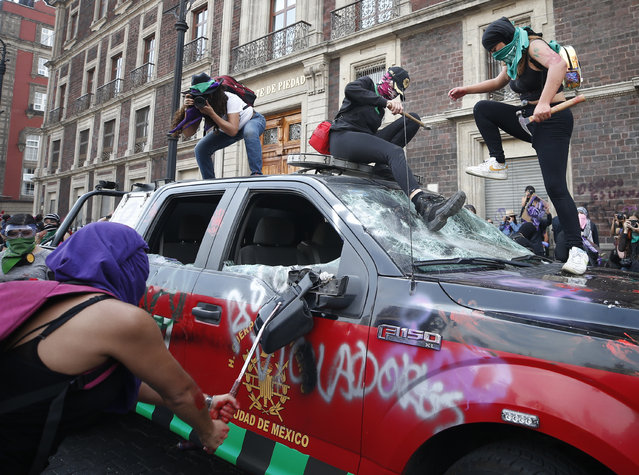 Demonstrators attack a vehicle belonging to the fire department during an International Women's Day march in Mexico City's main square, the Zocalo, Sunday, March 8, 2020. Protests against gender violence in Mexico have intensified in recent years amid an increase in killings of women and girls. (Photo by Rebecca Blackwell/AP Photo)