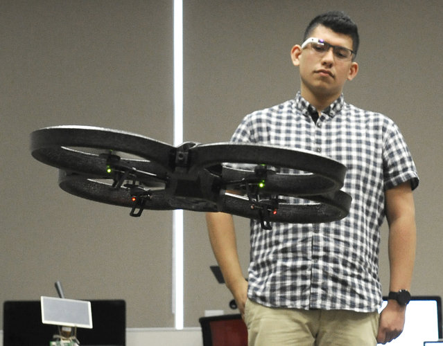 In this October 8, 2014 photo, undergraduate researcher Christopher Rios uses Google Glass to control a drone in mechanical engineering professor Ahmed Mahdy's classroom at Texas A&M Corpus Christi, in Corpus Christi, Texas. (Photo by Pat Sullivan/AP Photo)