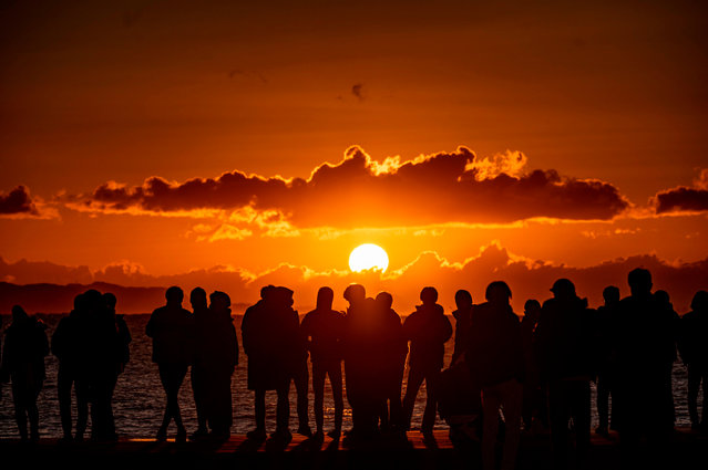 People gather at Southern Beach of Chigasaki to watch the sunrise on New Year's Day in Kanagawa Prefecture, southwest of Tokyo on January 1, 2021. (Photo by Philip Fong/AFP Photo)