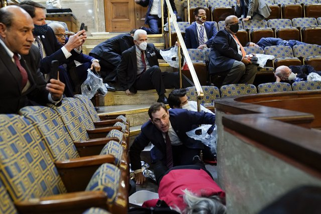 People shelter in the House gallery as protesters try to break into the House Chamber at the U.S. Capitol on Wednesday, January 6, 2021, in Washington. (Photo by Andrew Harnik/AP Photo)