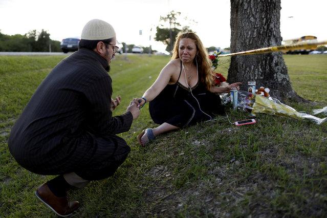 Daniel Hernandez, a local imam, comforts Dih-Anaa Forero of Missouri City, near the site of the shooting at the Santa Fe High School, in Santa Fe, Texas, U.S., May 19, 2018. (Photo by Jonathan Bachman/Reuters)