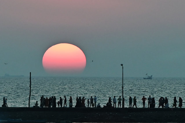 People walk along the seafront as the sun sets near Haji Ali mosque in Mumbai on November 23, 2020. (Photo by Punit Paranjpe/AFP Photo)