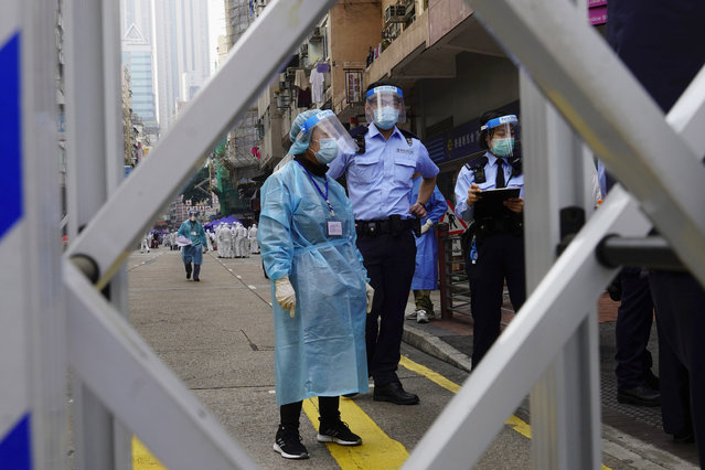Police officers and health officials stand guard at the Yau Ma Tei area, in Hong Kong, Saturday, January 23, 2021. Thousands of Hong Kong residents were locked down Saturday in an unprecedented move to contain a worsening outbreak in the city, authorities said. (Photo by Vincent Yu/AP Photo)