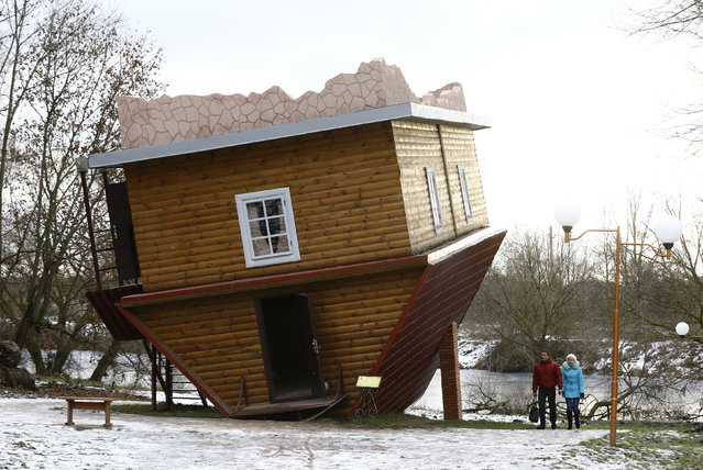 People walk outside an upside-down house in a tourist complex, near the village of Dukora, Belarus, December 2, 2015. Inside the house all objects are set up upside-down in order to create a special perspective for the visitors. (Photo by Vasily Fedosenko/Reuters)