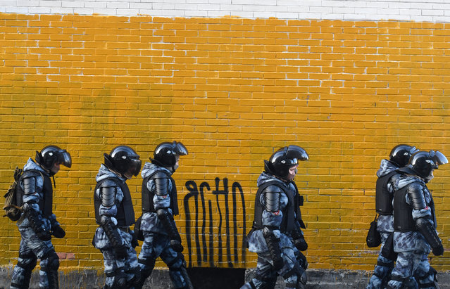 Law enforcement officers walk past a wall near the Moscow City Court during the trial of Russian opposition leader Alexei Navalny, charged with violating the terms of a 2014 suspended sentence for embezzlement, in Moscow on February 2, 2021. (Photo by Natalia Kolesnikova/AFP Photo)
