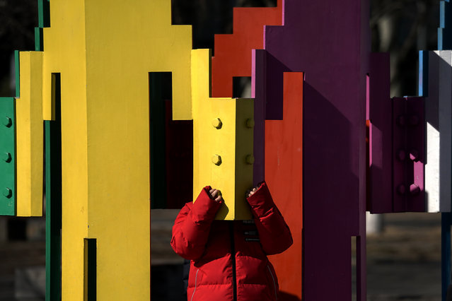 A child plays at a colorful human tower art installation on the Olympic Park in Beijing, Tuesday, February 2, 2021. China has largely stopped domestic transmission of the virus through sometimes draconian measures, including strict testing and electronic surveillance. Mask wearing in public is standard and lockdowns are routinely imposed on communities and even entire cities where cases are detected. (Photo by Andy Wong/AP Photo)