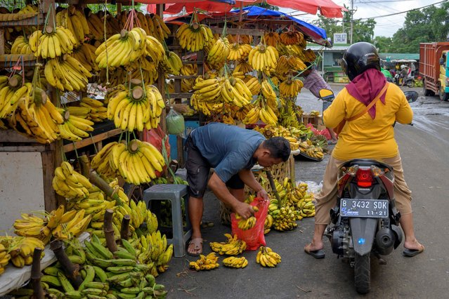 This picture taken on February 3, 2021 shows a vendor packaging bananas bought by a customer at a market in Jakarta. (Photo by Bay Ismoyo/AFP Photo)