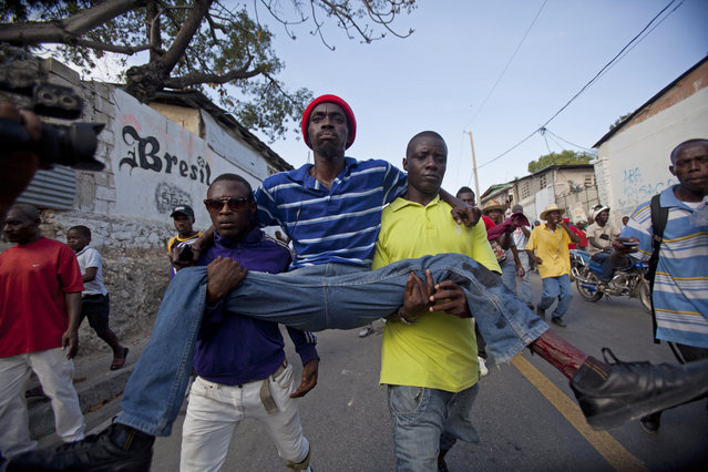 Protesters carry a man who was shot in his left leg after clashes broke out with national police during a demonstration to demand the resignation of President Michel Martelly, in Port-au-Prince, Haiti. Saturday, January 17, 2015. (Photo by Dieu Nalio Chery/AP Photo)
