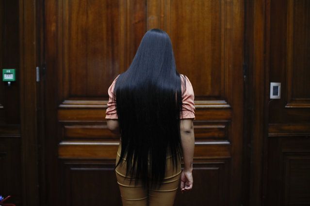 Transgender woman Angeles Rojas enters a room at Banco Nación where she works in Buenos Aires, Argentina, Thursday, November 5, 2020. Rojas, 23, joined the most important public bank in Argentina this year as part of the trans labor quota that is part of the public policies in favor of the LGBT community that the South American country has implemented in the last decade. (Photo by Natacha Pisarenko/AP Photo)