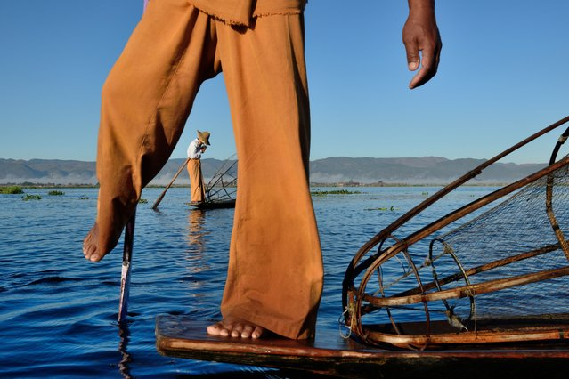 """""""Cigarette break"""". A fisherman on Inle lake (Myanmar) lights a cigarette while his colleague in front poses for tourists. (Photo and caption by Luka Esenko/National Geographic Traveler Photo Contest)"""