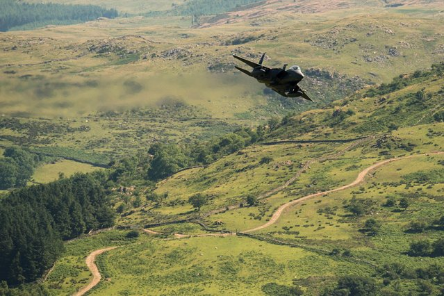 """A United States Air Force (USAF) F-15 fighter jet travels at low altitude through the """"Mach Loop"""" series of valleys near Dolgellau, north Wales on June 26, 2018. The Mach Loop valleys, situated between Dolgellau and Machynlleth, are regularly used by the military for operational low flying training which can take place as low as 76 metres from the nearest terrain. The USAF regularly use the loop to practice low-altitude flight, which confuses radar systems. The $93 million craft features a navigation pod containing a terrain-following radar which allows the jets to fly safely at very low altitudes. Its cutting-edge laser targeting system allows an enemy to be selected for destruction from a distance of 10 miles. It carries the most air-to-ground weapons of any US air force craft including Sidewinder missiles, advanced Air-to-Air Missiles and 20mm cannon with 500 rounds – used against enemy aircraft and """"soft"""" ground targets. (Photo by Oli Scarff/AFP Photo)"""
