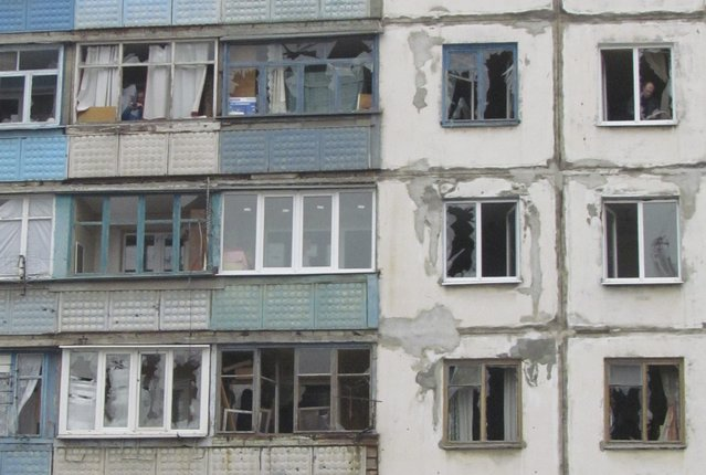 People look out of the windows of a residential block damaged by a recent shelling in Mariupol, eastern Ukraine, January 24, 2015. (Photo by Nikolai Ryabchenko/Reuters)