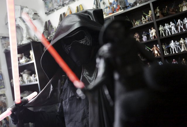 Mexican collector Pablo Perez, dressed as Star Wars character Kylo Ren, poses next to a toy collection of Star Wars characters and items at his home in Monterrey, Mexico December 12, 2015. Perez has collected more than 3,000 toys and items from the Star Wars movie series over 10 years, local media reported. (Photo by Daniel Becerril/Reuters)