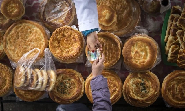 A customer (bottom) hands over money to a bread vendor at the Green Bazaar in Almaty January 23, 2015. (Photo by Shamil Zhumatov/Reuters)
