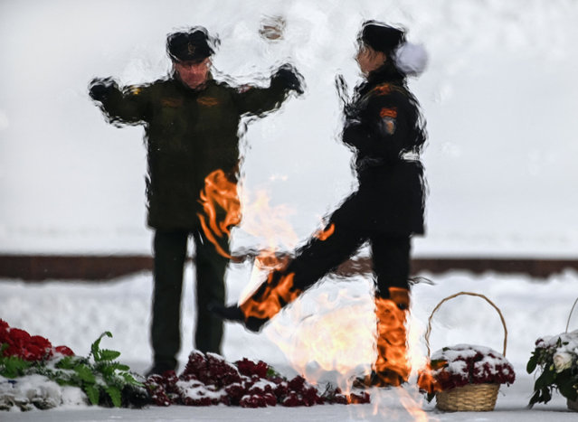 A Russian female military cadet marches in front of the Eternal Flame at the WWII memorial complex at Poklonnaya Hill in Moscow on February 17, 2021, during a rehearsal for the upcoming February 23's Defender of the Fatherland Day. (Photo by Alexander Nemenov/AFP Photo)