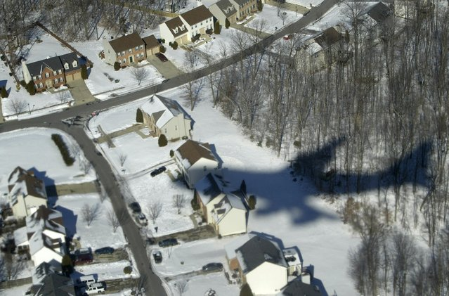 Air Force One casts its shadow over snow-covered houses in Waldorf, Maryland, in this January 31, 2004 file photo. (Photo by Jason Reed/Reuters)