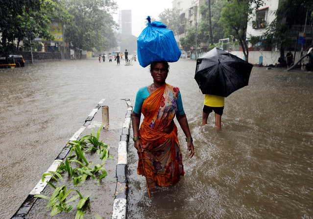 People wade through a waterlogged street during heavy rains in Mumbai, July 8, 2018. (Photo by Danish Siddiqui/Reuters)