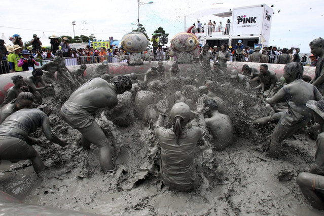 Participants play in a mud pool during the Boryeong Mud Festival at Daecheon Beach in Boryeong, South Korea, Saturday, July 20, 2013. The 16th annual mud festival features mud wrestling and mud sliding. (Photo by Ahn Young-joon/AP Photo)