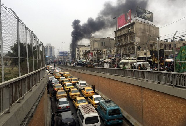 Smoke rises from the site of a bomb attack in Baghdad January 30, 2015. At least 12 civilians were killed on Friday morning when two bombs exploded in central Baghdad, security sources said. An initial blast in the Bab al-Sharqi district was followed by a car bomb, the sources said. At least 30 people were also wounded in the attack. (Photo by Ahmad Mousa/Reuters)