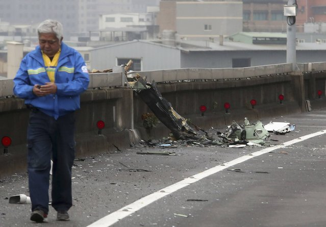 A man walks past next to the wreckage of a TransAsia Airways plane which hit a motorway before crash landing in a river, in New Taipei City, February 4, 2015. (Photo by Reuters/Stringer)