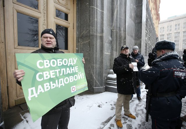 Yabloko (Apple) political party leader Sergei Mitrokhin (L) attends a rally in support of Svetlana Davydova, who was detained on suspicion of treason, as a policeman checks the documents of participants near the Federal Security Service headquarters in central Moscow, February 3, 2015. (Photo by Sergei Karpukhin/Reuters)