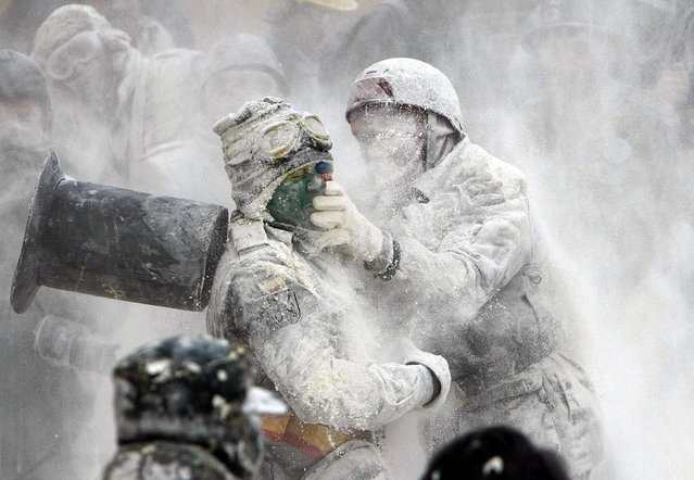 "People take part in the flour fight as part of the winter festival in Ibi, Alicante, eastern Spain, 28 December 2015. Around one thousand people attended the feast during which some known as ""els enfarinats"" (the floured ones) take part in a street fight, throwing flour, eggs and firecrackers at each other. (Photo by Morell/EPA)"