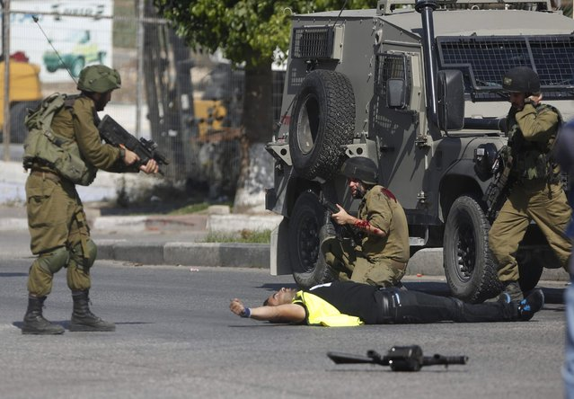 """An Israeli soldier shoots a Palestinian holding a knife after he stabbed another Israeli soldier, seen kneeling, during clashes in Hebron, West Bank, October 16, 2015. The Palestinian man wearing a yellow """"press"""" vest and a T-shirt identifying him as journalist stabbed and wounded the soldier in the latest in a monthlong spate of attacks. (Photo by Nasser Shiyoukhi/AP Photo)"""