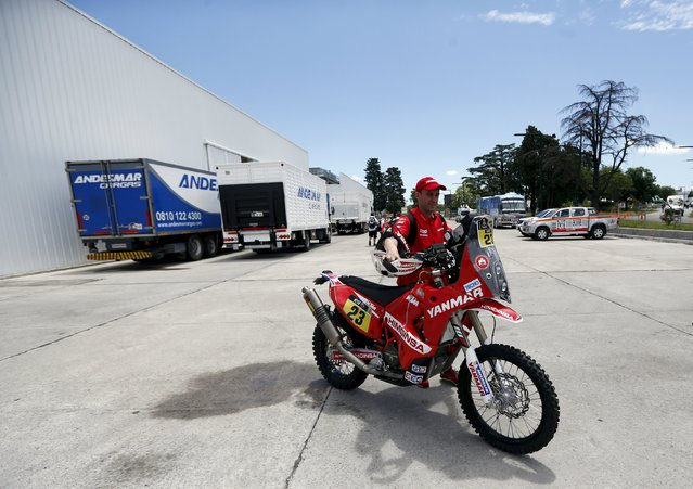Gerard Farres of Spain pushes his KTM motorcycle as he leaves the technical verification area ahead of the Dakar Rally 2016 in Buenos Aires, Argentina, January 1, 2016. (Photo by Marcos Brindicci/Reuters)