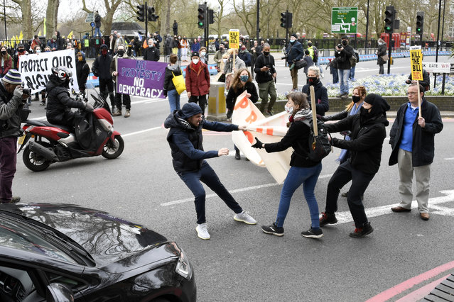 """A man tries to rip a banner held by demonstrators blocking traffic during a """"Kill the Bill"""" protest in London, Saturday, April 3, 2021. The banner read Protect The Right To Protest. (Photo by Alberto Pezzali/AP Photo)"""