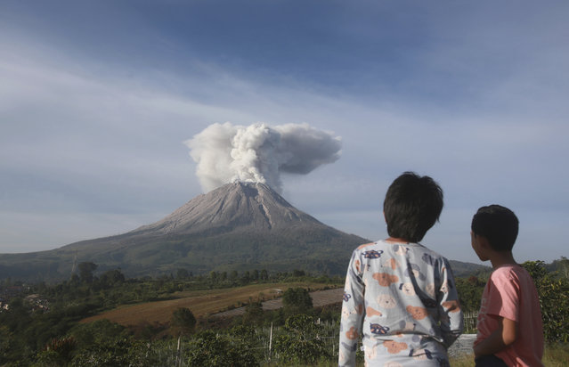 Indonesian youths watch as Mount Sinabung spews volcanic materials during an eruption in Karo, North Sumatra, Indonesia, Thursday, March 11, 2021. The volcano unleashed an avalanche of searing gas clouds flowing down its slopes during eruption on Thursday. No casualties were reported. (Photo by Binsar Bakkara/AP Photo)