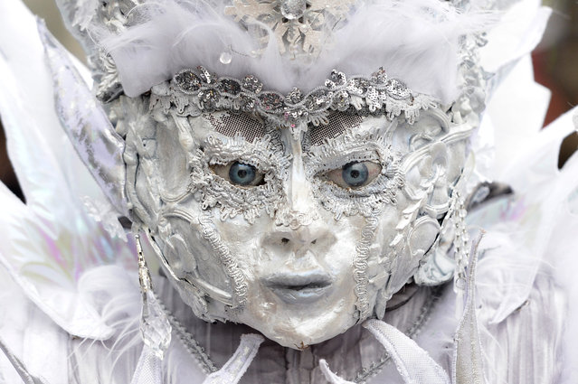 A masked participant  walks  through the streets during the  carnival parade  in Lucerne, Switzerland, Monday, February 16, 2015. (Photo by Urs Flueeler/AP Photo/Keyston)