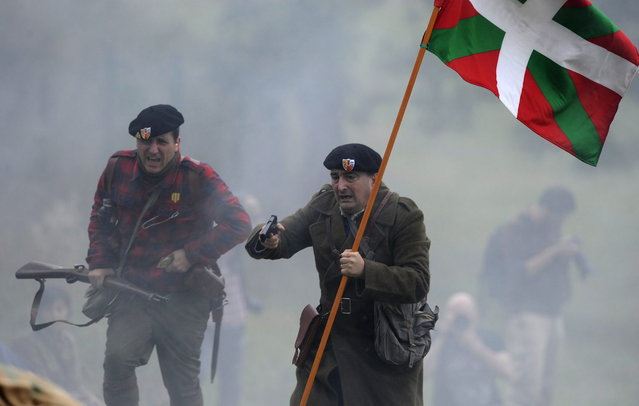 """Aitor Esteban, a deputy of the PNV (National Basque Party), holds a gun and an """"ikurrina"""" flag during a re-enactment of the """"Battle of Areces"""" that took place during the Spanish Civil War, in Grullos, north of Spain, September 14, 2013. The re-enactment of the historic 1937 battle was organised by the Frente del Nalon Association. (Photo by Eloy Alonso/Reuters)"""