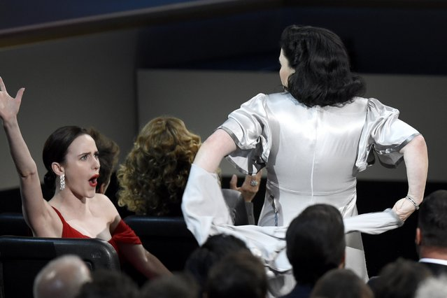 "Alex Borstein takes off a top layer of her dress before appearing on stage to accept the award for outstanding supporting actress in a comedy series for ""The Marvelous Mrs. Maisel"" at the 70th Primetime Emmy Awards on Monday, September 17, 2018, at the Microsoft Theater in Los Angeles. Cheering on at left is Rachel Brosnahan. (Photo by Chris Pizzello/Invision/AP Photo)"