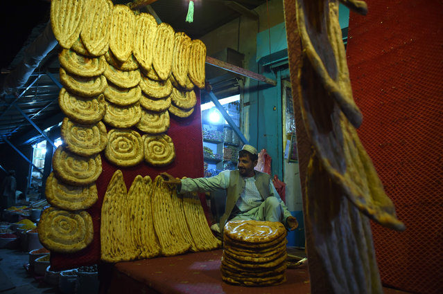In this photograph taken on October 4, 2016, an Afghan baker prepares bread at his shop as he waits for customers in Lashkar Gah, the capital city of Helmand province For years Helmand was the centerpiece of the Western military intervention in Afghanistan only for it to slip deeper into a quagmire of instability, with almost the entire southern province teetering on the verge of collapse. Intensified fighting has killed hundreds and forced thousands to flee to besieged capital Lashkar Gah, sparking a humanitarian crisis as the city – one of the last government- held enclaves – risks falling to the Taliban' s repeated ferocious assaults. (Photo by Wakil Kohsar/AFP Photo)