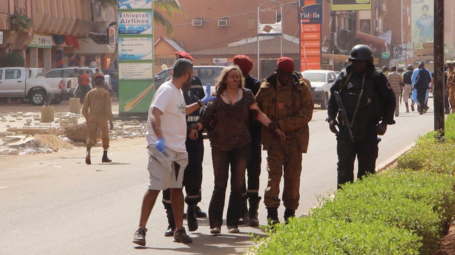 This image taken from AP television shows a woman being led to safety in Ouagadougou, Burkina Faso, Saturday January 16, 2016. The overnight seizure of a luxury hotel in Burkina Faso's capital by al-Qaida-linked extremists ended Saturday when Burkina Faso and French security forces killed four jihadist attackers and freed more than 126 people, the West African nation's president said. (Photo by AP Photo)