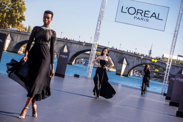 Models present creations on the catwalk as part of a fashion show organized by cosmetics company L'Oreal on the Seine, during the Paris Fashion Week, in Paris, France, 30 September 2018. (Photo by Christophe Petit Tesson/EPA/EFE)
