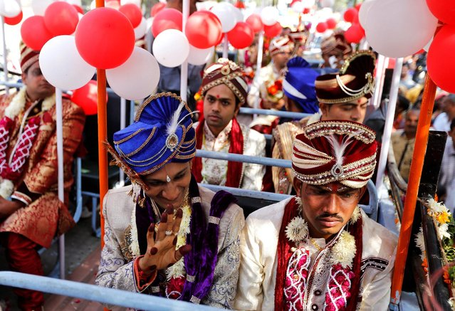 A groom waves to his relatives from an open bus as he arrives to take part in a mass wedding in Ahmedabad, India, December 4, 2016. (Photo by Amit Dave/Reuters)